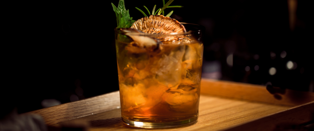 A spiced gingerbread cocktail with herbs and ice