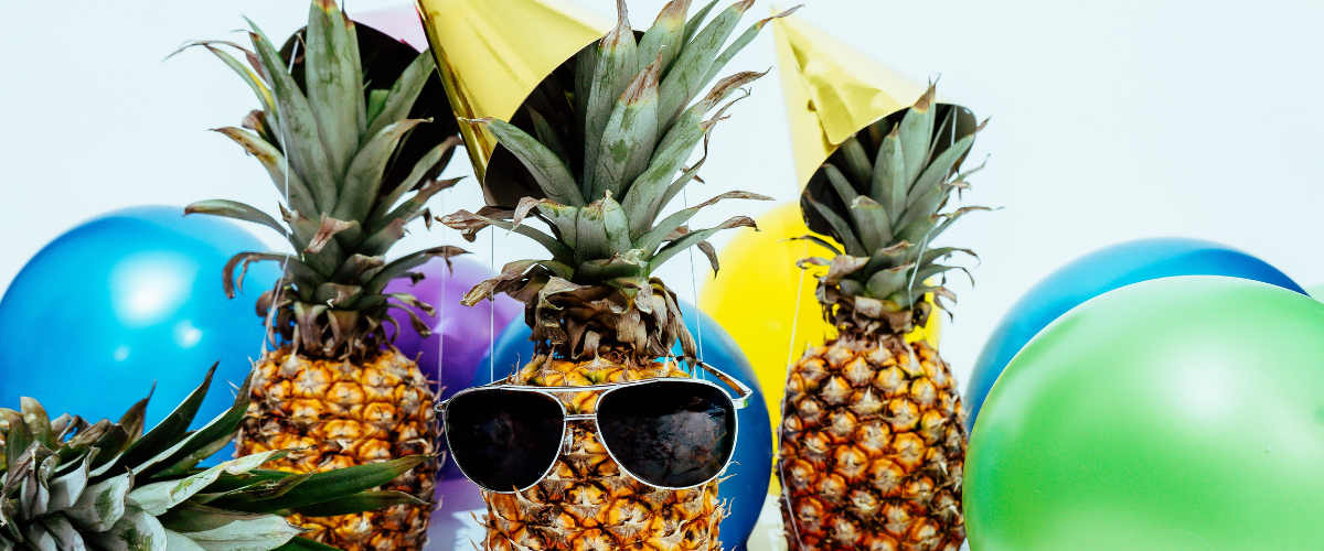 Festive Pineapples wearing glasses and balloons in background